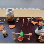 ryba na ohni, zbraně, pračlověk, náhrdelník, střepy a malý mamut
